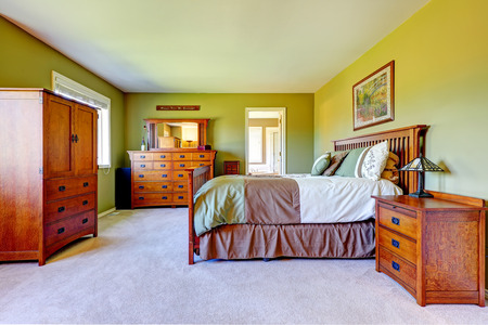 nightstand: Master bedroom interior in bright green color with wooden bed, nightstand, bedroom vanity cabinet and wardrobe.
