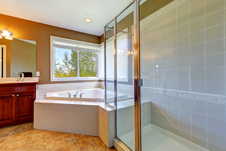 Bathroom interior with corner bath tub and screened shower. Tile floor and white tile wall trim