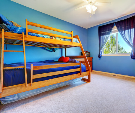 Bright blue bedroom for kids with wooden bulk bed and nightstand