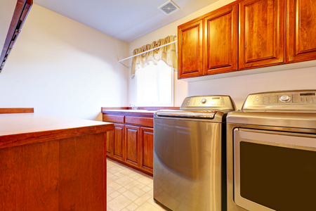 Laundry room with modern steel appliances and brown storage combination Stock Photo