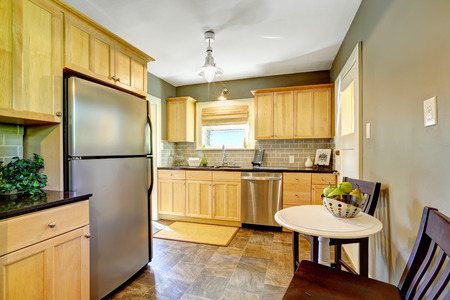 refrigerator kitchen: Small kitchen room with maple storage cabinet, steel dishwasher and refrigerator. Room has white table and two chairs Stock Photo