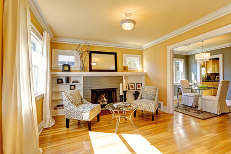 Family room with cozy sitting area. Two chairs and glass top coffe table. Room decorated with dry bushes
