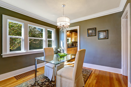 dining table and chairs: Dining room interior with dark grey walls and hardwood floor. Table with glass top and two elegant chairs