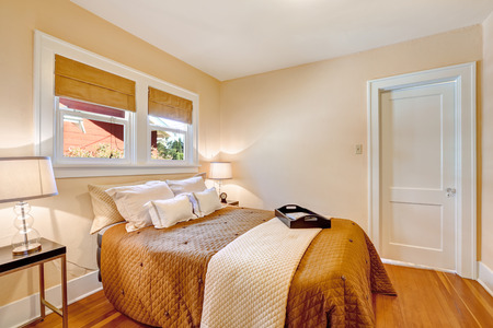 Warm bedroom interior with light color walls and hardwood floor. Bed with brown bedding, ivory blanket and pillows