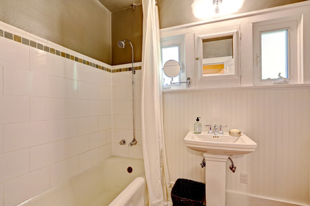 white trim: Simple bathroom interior with washbasin stand and bath tub. Dark brown wall with white tile trim and plank panel tirm
