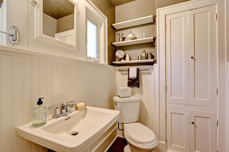 Simple bathroom interior in white color with washbasin stand and toilet.