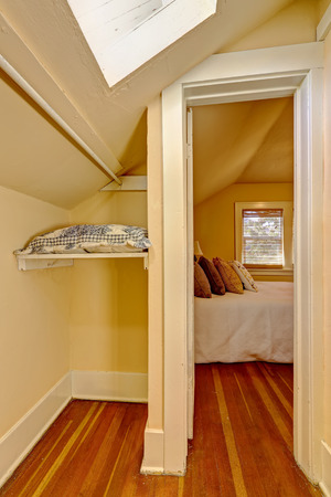 walk in closet: Small empty walk in closet interior with vaulted ceiling and skylight.