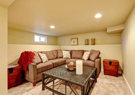 Cozy family room with brown comfortable sofa and wicker table. Room with light ivory walls and carpet floor