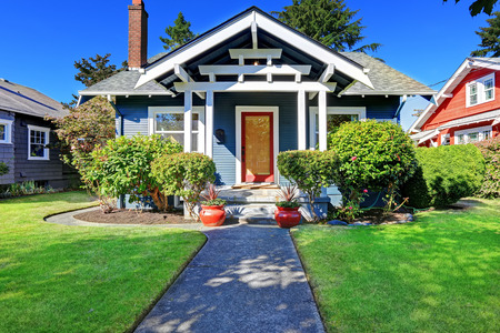 Simple house exterior with tile roof. Front porch with curb appeal