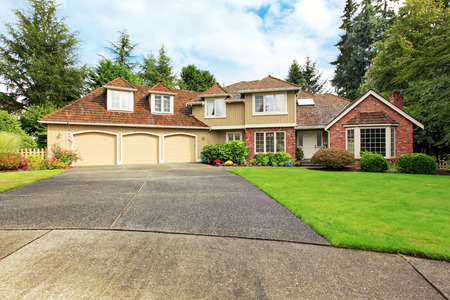 Luxury house exterior with brick trim, tile roof and french windows. House with three car garage