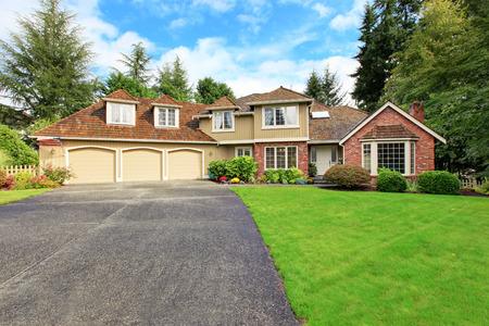 Luxe huis buitenkant met bakstenen trim, dakpannen en openslaande deuren. Huis met drie auto garage en asfalt oprit Stockfoto