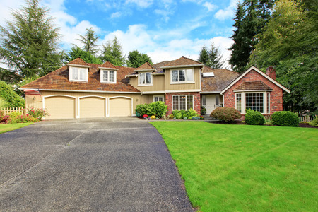 Luxury house exterior with brick trim, tile roof and french windows. House with three car garage and asphalt driveway