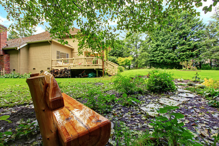 House with walkout deck. Backyard outdoor rest area with wooden bench photo