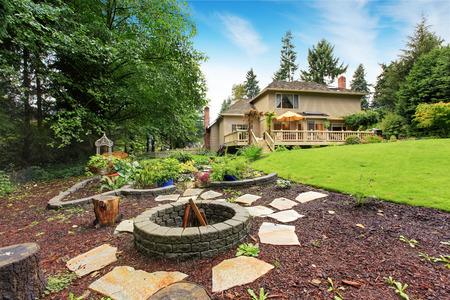 広々 とした裏庭領域の家。庭のベッドおよび火ピット