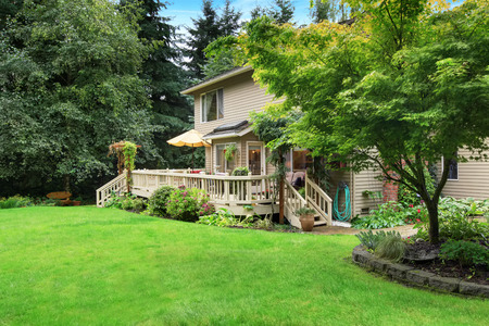 Cozy walkout deck with patio area and backyard landscape Stock Photo