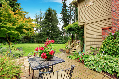 Backyard with tile foor patio area, iron table set decorated with flower pot