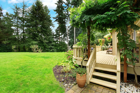 wood deck: Wooden walkout deck with stairs overlooking backyard landscape Stock Photo
