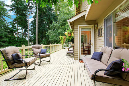 Wooden walkout deck with sitting area overlooking backyard landscape