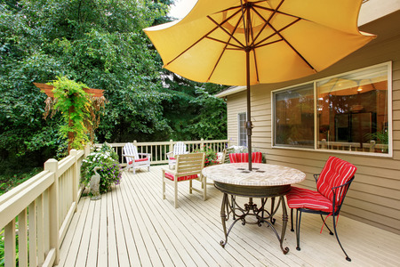 Wooden walkout deck with patio table, umbrella and chairs