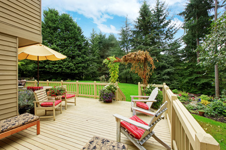 Wooden walkout deck with deck chairs. Deck overlooking backyard landscape Foto de archivo