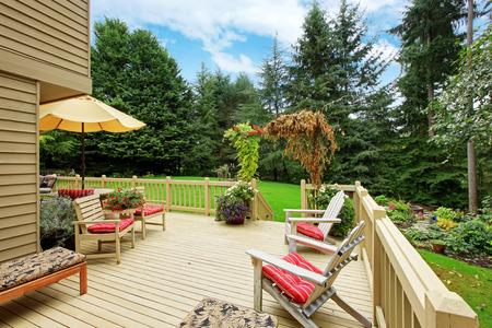 Wooden Walkout Deck With Deck Chairs. Deck Overlooking Backyard Landscape  Photo
