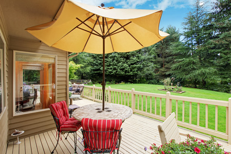 Wooden walkout deck with patio table, umbrella and chairs overlooking backyard landscape Stock Photo