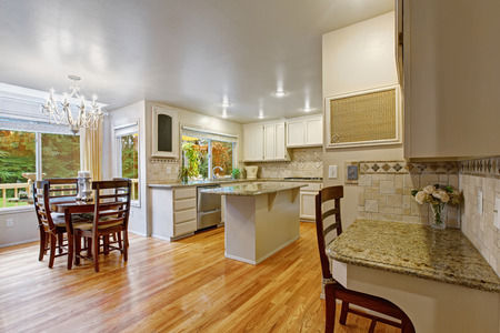 counter top: Bright kitchen room with white storage combination and granite tops. Room has wooden table set decorated with candles