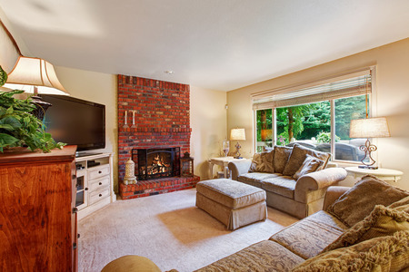 Bright ivory living room with brick background fireplace and comfortable couch with tv