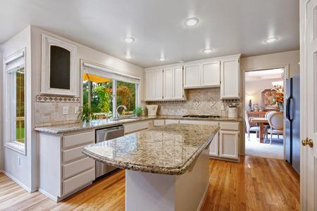 Küche Zimmer mit weißen Aufbewahrungskombination. Kücheninsel mit Granitplatte