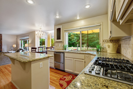 Kitchen with white storage combination and kitchen island. Cabinet with granite tops Stock Photo