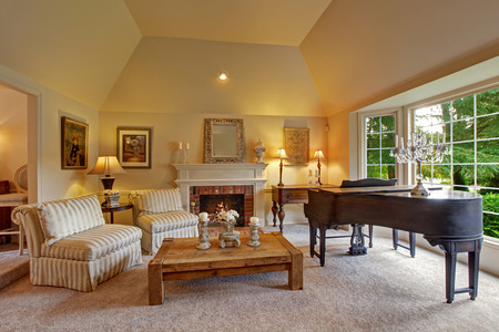Luxury family room with high vaulted ceiling and large french window. Room has grand piano, fireplace, striped chairs and wooden coffee table Stock Photo