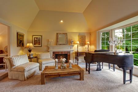 Luxus Familienzimmer mit hohen Gewölbedecke und großen französisch-Fenster. Zimmer hat Flügel, Kamin, gestreiften Sesseln und Couchtisch aus Holz Lizenzfreie Bilder
