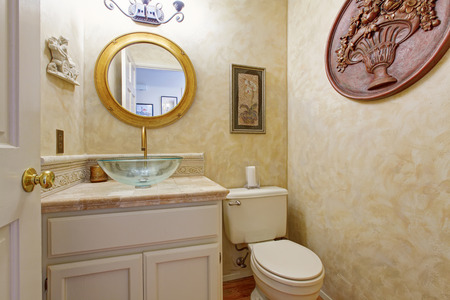 Bathroom interior in creamy tone. White bathroom cabinet with glass vessel sink and round mirror