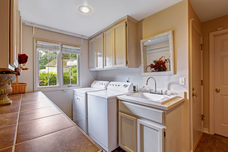 Laundry room with window and standard appliances. Room has cabinets and sink photo