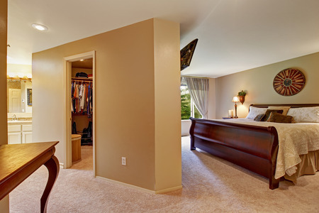 walk in closet: Spacious bedroom interior with walk in closet and queen size nice wooden bed Stock Photo