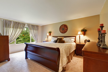 nightstands: Spacious bedroom interior with queen size nice wooden bed, nightstands and cabinet decorated with candles