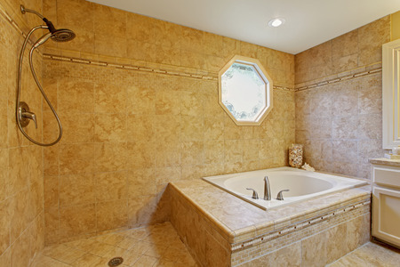 Luxury bathroom interior. White bath tub with tile trim and open shower