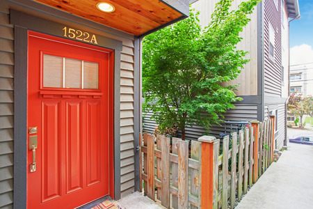 House exterior with low wooden fence. View of entrance porch with bright red door Stock Photo