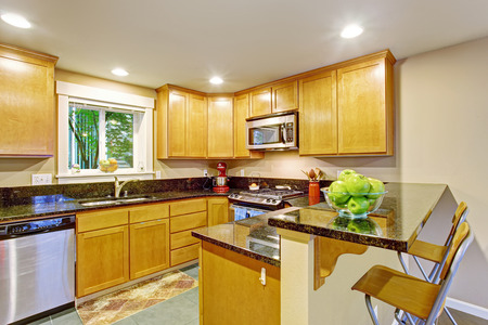 black appliances: Kitchen inteiror. Maple storage combination with steel appliances and black counter tops
