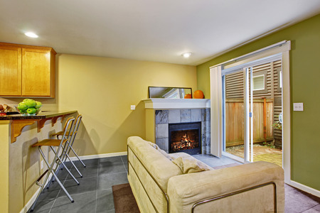 Cozy sitting area with fireplace and glass sliding doors to backyard area