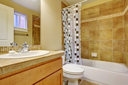 Beige tone bathroom interior with tile wall trim. Vanity cabinet with mirror. Bath tub decorated with curtain Stock Photo