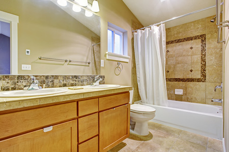 bathroom mirror: Beige tone bathroom interior with tile wall trim. Vanity cabinet with two sinks and mirror. Bath tub decorated with white curtain