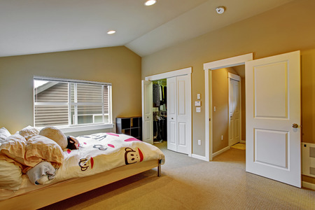 Cozy bedroom with high vaulted ceiling and walk in closet. Light wooden bed with white cheerful bedding photo