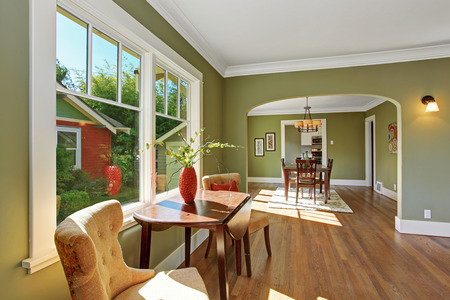 House interior with open floor plan. Sitting area by the window with table and chairs and dining room with archway
