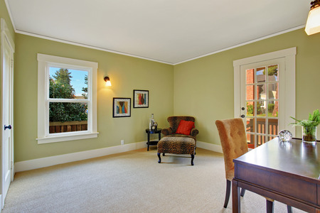 Light green office room with desk and sitting area in the corner with leopard armchair and small table