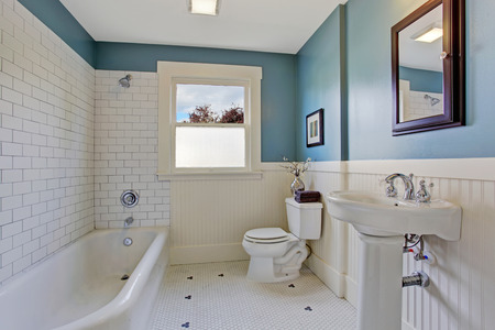Bathroom interior with blue wall and white plank panel trim. Bath tub with tile wall trim.