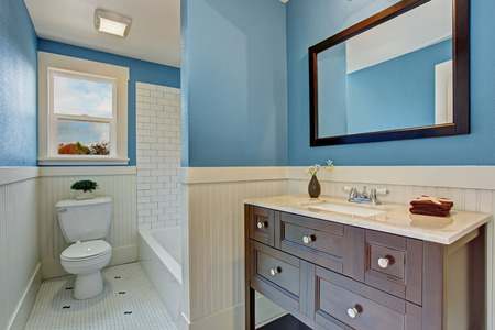 white trim: Bathroom interior with blue wall and white plank panel trim. Bath tub with tile wall trim. Brown vanity cabinet with mirror Stock Photo