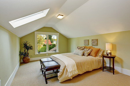 Light mint bedroom interior with white vaulted ceiling and skylight. Room has queen size bed, ottoman and table