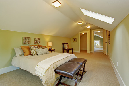 Spacious light mint bedroom interior with vaulted ceiling, skylight. Furnished with queen bedroom and leather ottoman Stock Photo
