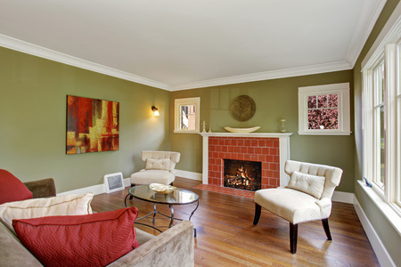 Olive tone family room with fireplace, two white chairs, sofa and glass top coffee table